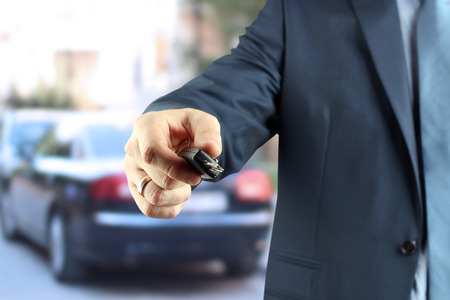 lock: Young successful businessman offering a car key.