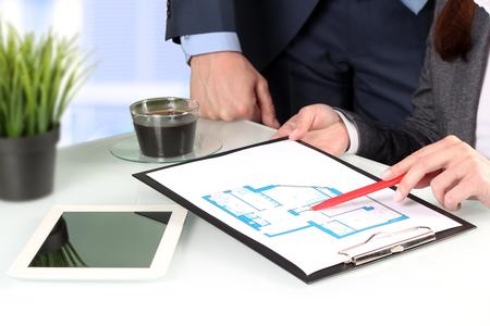zakelijk: Makelaar Resultaat huis plannen om een businesssman. Focus op een pen en hand