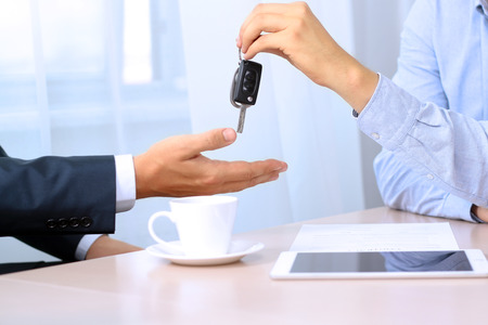 Car salesman handing over the keys for a new car to a young businessman. Focus on a key