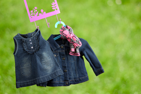 shoulder buttons: Fashion baby dresses hanging on a hanger on a green  background Stock Photo