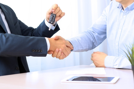 office view: Car salesman handing over the keys for a new car to a young businessman . Handshake between two business people. Focus on a key