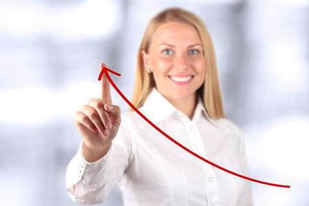 happy businesswoman: Businesswoman  touching a   virtual Graph by hand.  Blue background beside Stock Photo