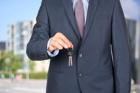 trade secret: Cropped image of estate agent giving house keys outside Stock Photo