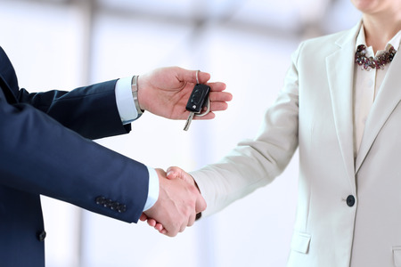 buying a car: Car saleswoman handing over the keys for a new car to a young businessman . Handshake between two business people Stock Photo