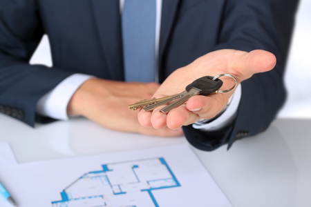 estate: Real-estate agent giving  a house  key. The plan of a flat behind Stock Photo