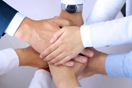work group: Close-up of business partners making pile of hands at meeting