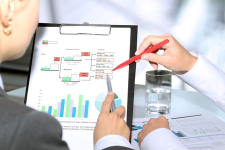 a study: Business colleagues working and analyzing financial figures on a graphs Stock Photo