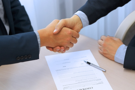 contrato de trabajo: Primer plano imagen de un apretón de manos entre dos colegas después de firmar un contrato