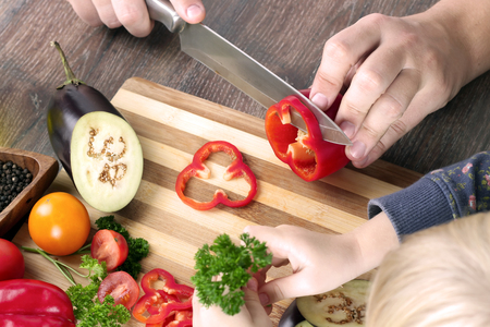 food, family, cooking and people concept - Man chopping paprika on cutting board with knife in kitchen with daughter