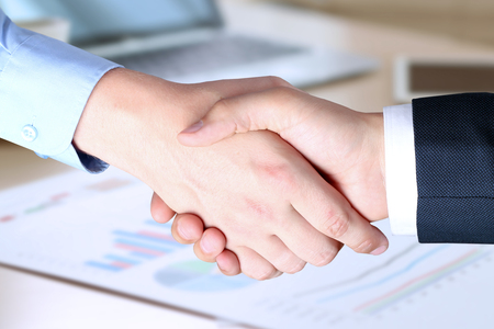 The Close-up image of a firm handshake between two colleagues in office.