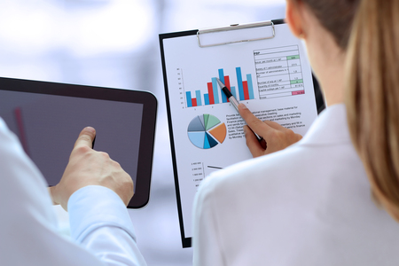 information analysis: Business colleagues working and analyzing financial figures on a graphs Stock Photo