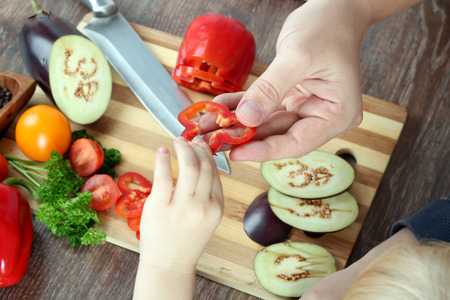 niños cocinando: la comida, la familia, la cocina y la gente concepto - Hombre dando pimentón a la hija