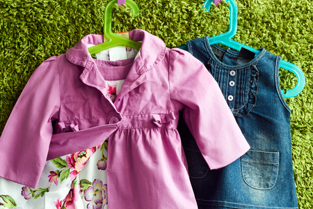 shoulder buttons: Fashion baby dress and coat  hanging on a hanger on a green summer background