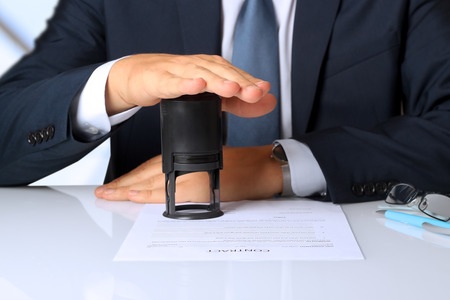 job satisfaction: Close-up Of Businessman Hand Pressing a Stamp On Document in the office
