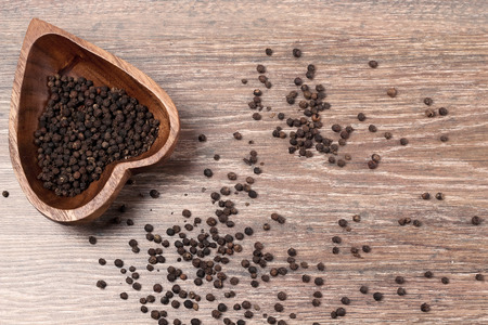 milled black pepper ,Black pepper corns on an old wooden background
