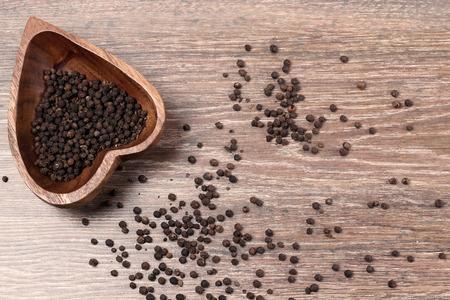 pepe nero: pepe nero macinato, nero grani di pepe su un fondo in legno vecchio