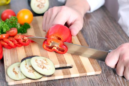 nice food: еда, семья, кулинария и люди концепции - Человек измельчения перец на разделочную доску с ножом на кухне