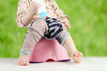 poo: Childrens legs hanging down from a chamber-pot on a green  background