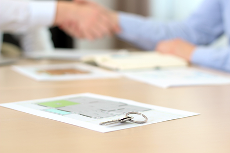 Real-estate agent signing a contract. Handshake.A  house key with project of a flat behind. Stock Photo
