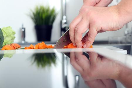 cuchillo: la comida, la familia, la cocina y la gente concepto - Hombre cortar una zanahoria en la tabla de cortar con un cuchillo en la cocina Foto de archivo