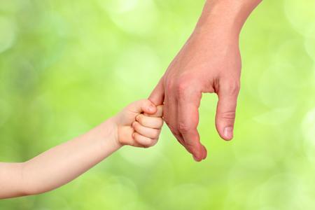 kinderen: een vader houdt de hand van een klein kind op een groene achtergrond Stockfoto