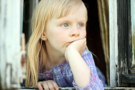 occhi tristi: grave bambina bionda guardando fuori dalla finestra Archivio Fotografico