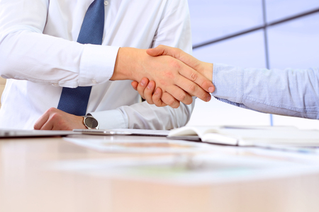 hands at work: Close-up image of a firm handshake between two colleagues after signing a contract