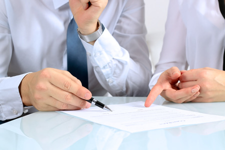 writing paper: Two business partners signing a document