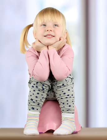 poo: Small  smily girl sits  on a potty