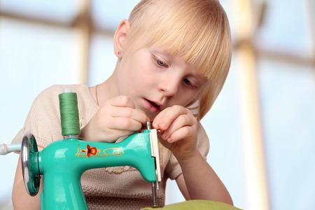 Mädchen nähen an einer Nähmaschine der Kinder. Standard-Bild - 52006014