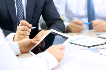 information analysis: business colleagues working together and analyzing financial figures on a digital tablet