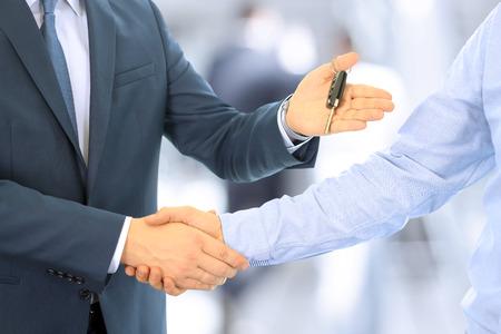 Venditore di auto consegna delle chiavi per una nuova auto a un giovane uomo d'affari. Stretta di mano tra due uomini d'affari. Focus su un tasto Archivio Fotografico - 52006018