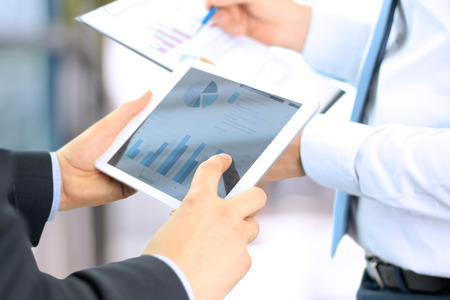 financial team: business colleagues working together and analyzing financial figures on a digital tablet