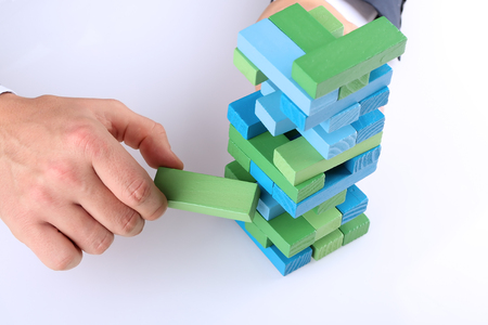 fragile economy: Planning, risk and strategy in business, businessman getting out a wooden block from a tower Stock Photo