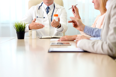 meds: hospital, medical education, health care, people and medicine concept - doctor showing meds to the  group of happy doctors at medical office Stock Photo
