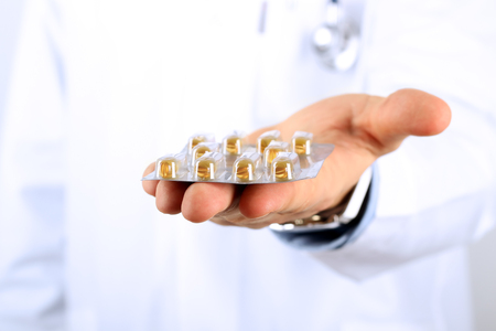 labcoat: Doctor in a white  labcoat giving  pills
