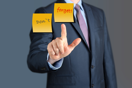 reminders: Businessman touching Dont Forget word.  business concept Stock Photo