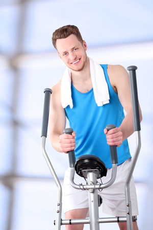 exercise machine: Sport man doing healthy Fitness with a Exercise Machine Stock Photo