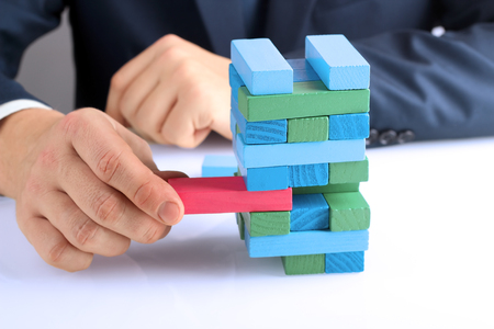 Planning, risk and strategy in business, businessman getting out a wooden block from a tower Standard-Bild