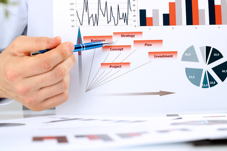 financial figures: business man  analyzing financial figures on a graphs Stock Photo