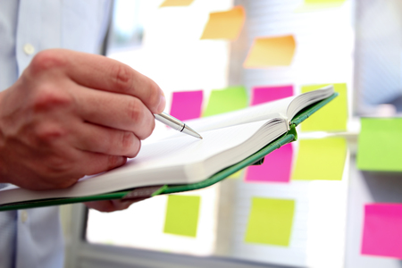 copybook: business man  working  with  copybook and stickers in office