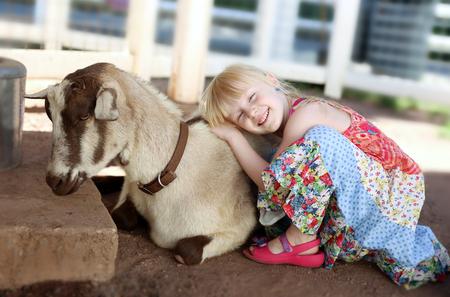 Little smiling  girl hugging the  goat