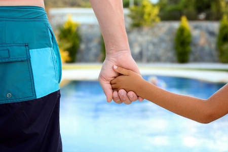generosidad: a father holds the hand of a small child on a blue  background Foto de archivo