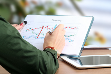oncept: young businesswoman working in the office,  sitting at her desk, analyzing  data in  graphics, pointing by pen.