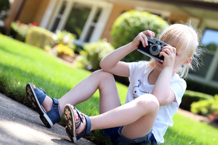 handheld device: Little girl taking picture using vintage film camera