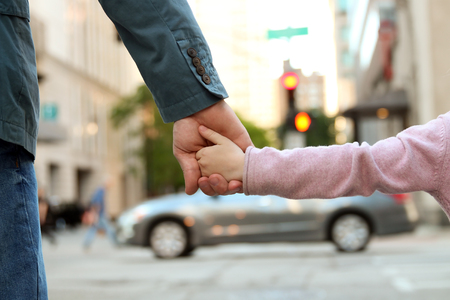 the traffic lights: father holding  the daughter child  hand  behind  the traffic lights Stock Photo