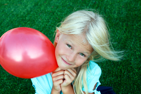 plead: beautiful blonde   girl siting on the grass and holding a red ball