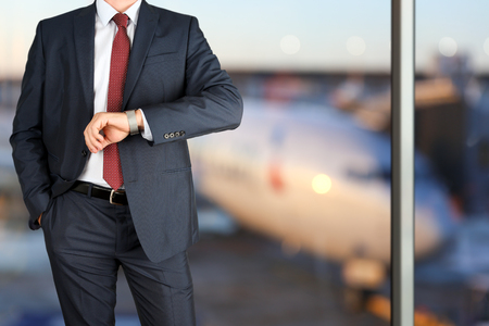 checking time: businessman checking time on his watch at the airport Stock Photo