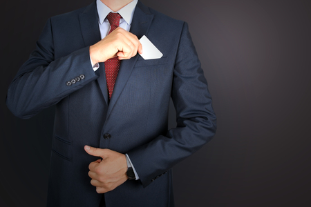 out of business: business man taking out business card from the pocket of business  modern suit