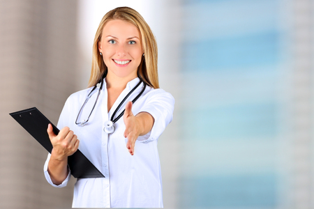 Image of beautiful   woman  doctor  looking at camera and giving a hand Stock Photo